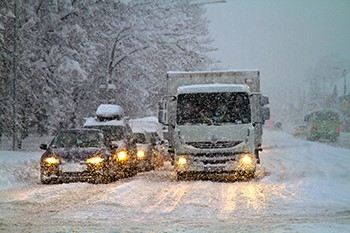 Photo of cars and trucks driving on a snow-packed road while more snow falls.
