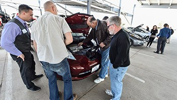 Four people look under the hood of a PEV at an electric vehicle ride and drive.