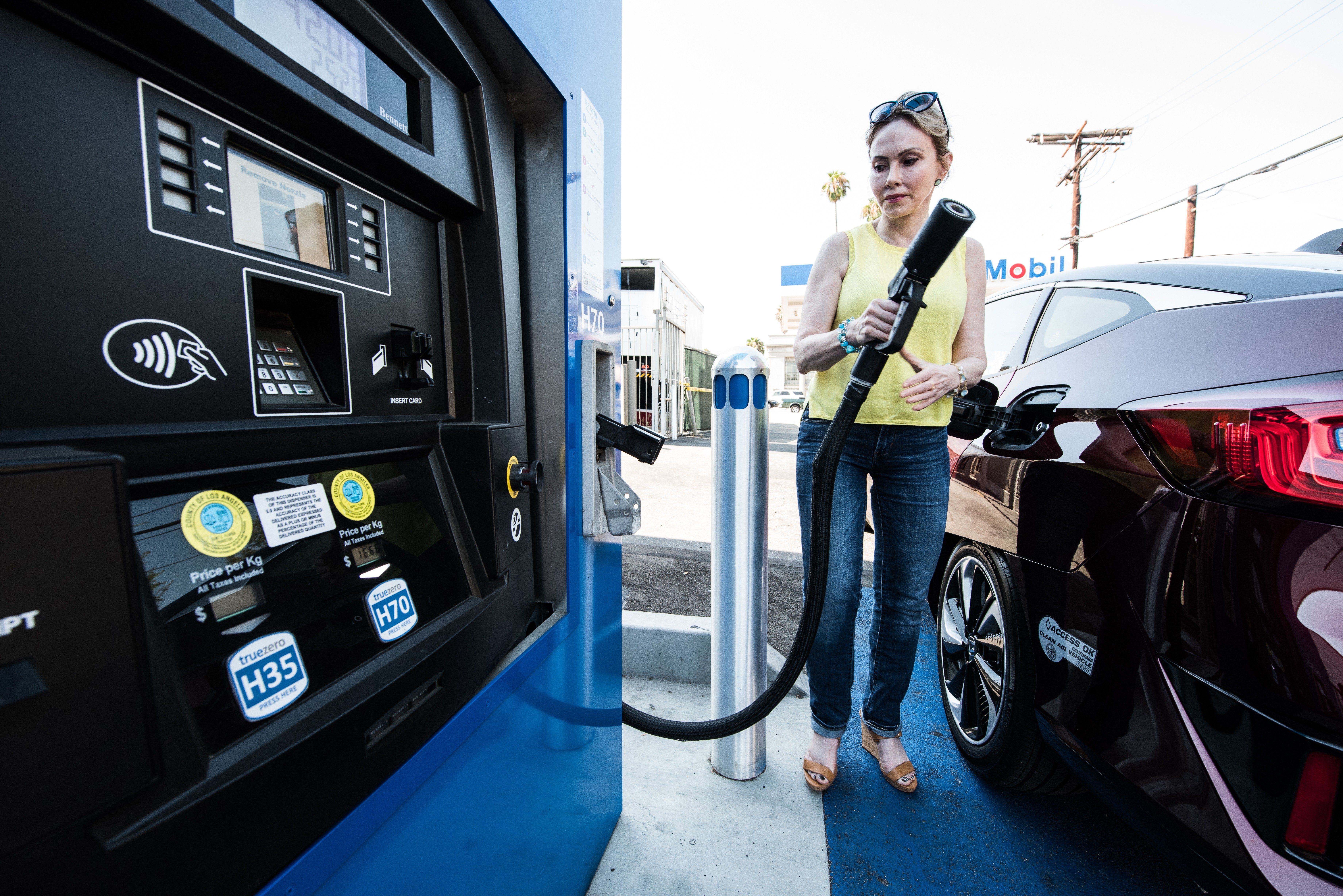 A photo of a woman fueling up her fuel cell electric vehicle.