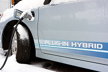 A photo of a plug-in electric vehicle charging in the snow.