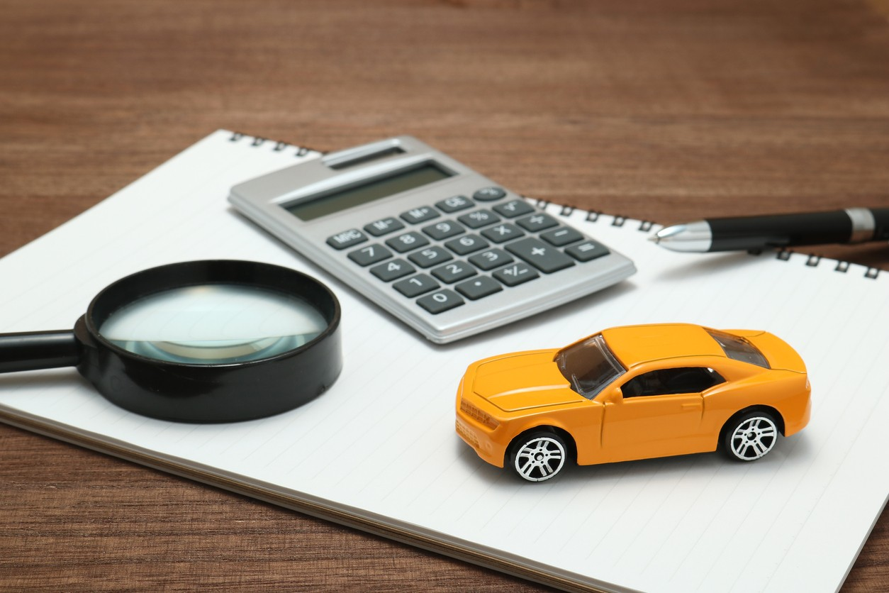 A photo of a toy car, calculator, and magnifying glass sitting on a piece of paper.