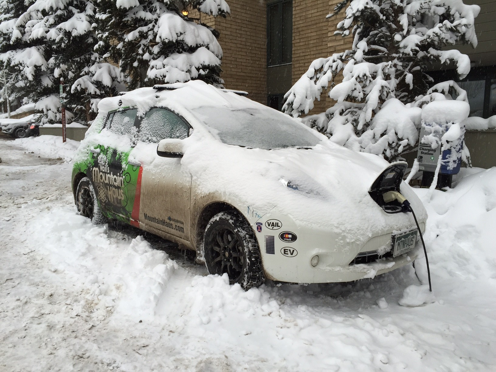 A photo of an electric vehicle charging in the snow.