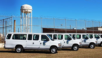 Photo of several propane vans parked outside a fenced prison facility.