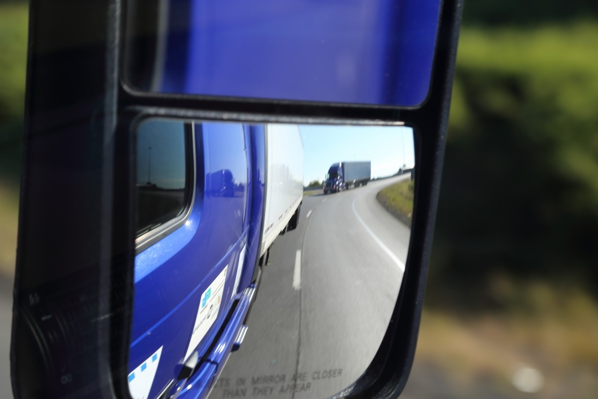 Photo of tractor-trailers reflected in a side view mirror.