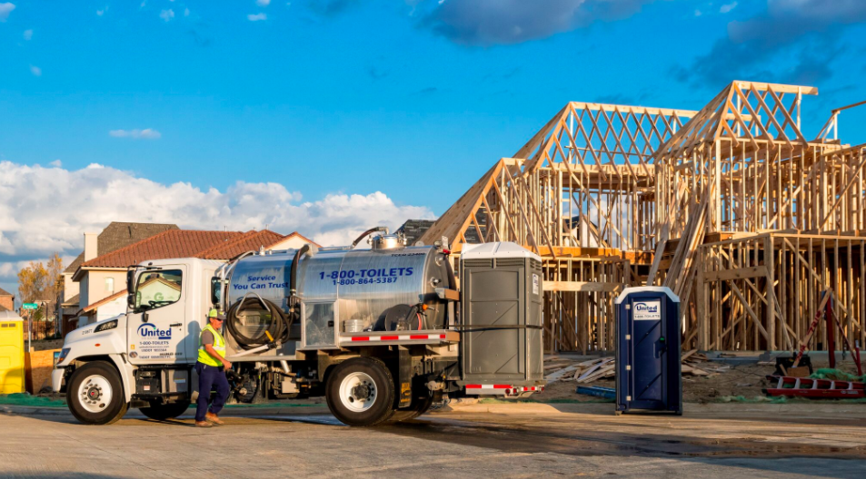 A photo of a construction worker with a tanker truck and portable restroom at a construction site.