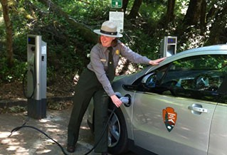 Photo of a woman plugging in an electric vehicle
