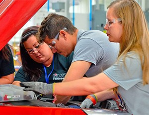 This photo shows three students from Rose-Hulman Institute of Technology working under the hood of their car.
