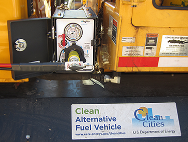 A close-up photo of a compressed natural gas truck with a white Clean Cities sticker refueling at a CNG station.