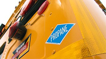 A photo of an orange school bus with a propane sticker on the back.