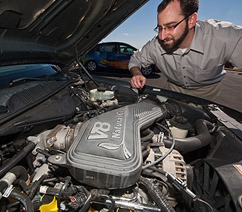 A photo a man in glasses standing over the open hood of a car with a natural gas engine.