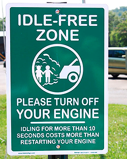 A photo of a green sign with white writing and a graphic showing a car with exhaust spewing out the tailpipe onto people.