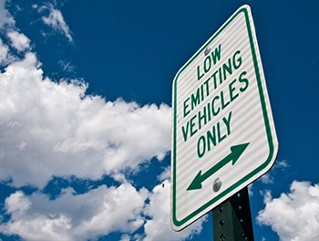 A photo of a white sign that reads 'Low emitting vehicles only' in green writing, set against a blue sky with white clouds.