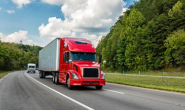 Photo of a red semi-truck driving on a highway surrounded by forest.