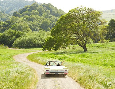 Photo of a couple in a silver convertible driving down a dirt road in the countryside.
