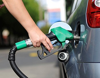 Photo of a person's hand using a green fuel nozzle to fill their car with biofuel.