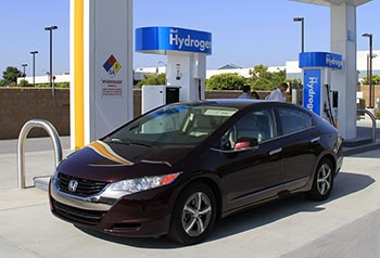 A photo of a dark maroon-colored sedan parked in front of a hydrogen fueling station.
