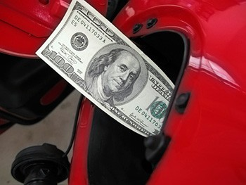 Photo of a one-hundred dollar bill sticking out of a fuel receptacle on a red car.