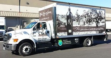 "Photo of a white truck with a wine bottle on the side and the company's name, ""Click"" on the cab door."