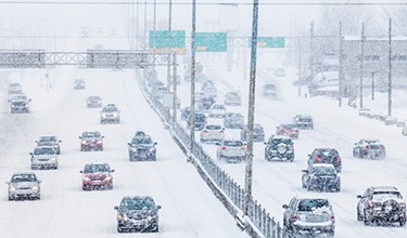 Photo of vehicles on the highway in a snowstorm.