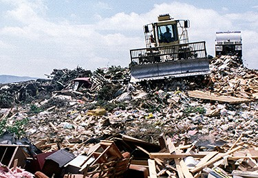 Photo of a garbage hauler in a dump.