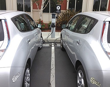 A photo of two silver electric vehicles charging.