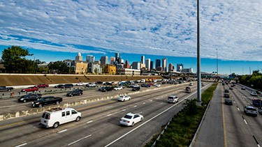 A photo of traffic on an interstate with a city in the background.