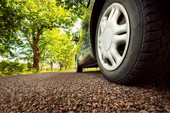 A close-up photo of a vehicle's tires on asphalt in the summer time.