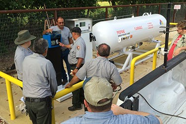 Photo of several men in national park uniforms gathered around a propane tank and electronic equipment attached to it.