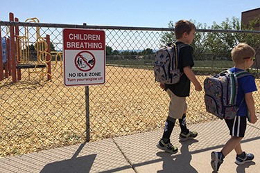 "Photo of two young boys with backpacks walking past a school sign that reads ""Children breathing - no idle zone. Turn your engine off."""