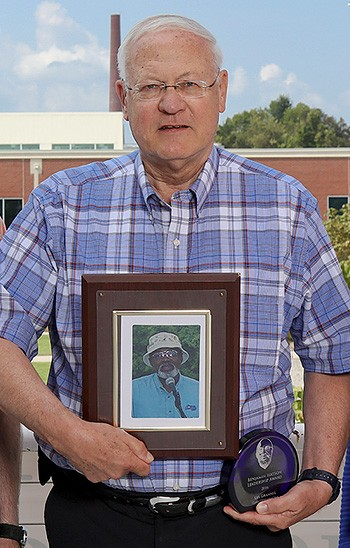 Photo of Mr. Lee Grannis standing holding his Benjamin Watson award and a framed photograph of Benjamin Watson.