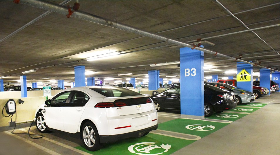A photo of a white EV sedan plugged in to a charging station located inside of an employee parking garage.